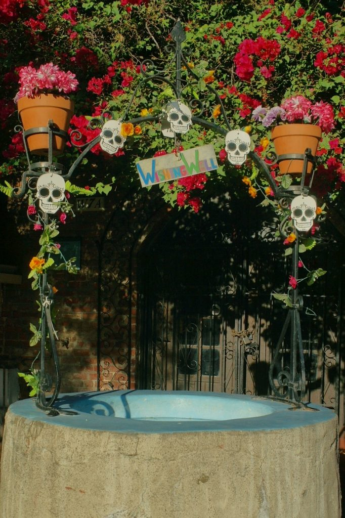 wishing-well decorated with flowers and Day of the Dead skull art