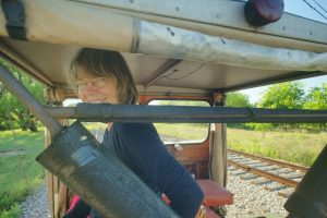 Alexis looking back over her shoulder from her seat on a railroad motor car