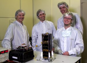 PicSat nanosatellite standing on table in front of four of the experiemnters who built it.